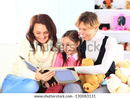 Grandmother, mother, and daughter reading a book together - stock photo