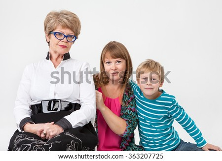 Grandmother, mother and son portrait on a gray background - stock photo
