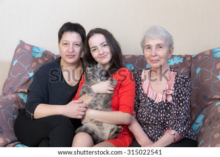 grandmother mother daughter and cat on a sofa