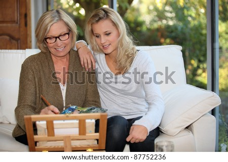 grandmother painting with granddaughter on her side - stock photo