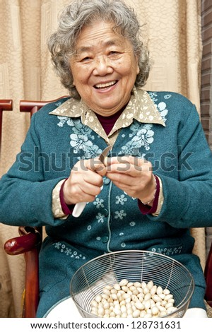Grandmother peeling nut fruit - stock photo