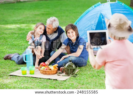 Grandmother photographing family through digital tablet at campsite - stock photo