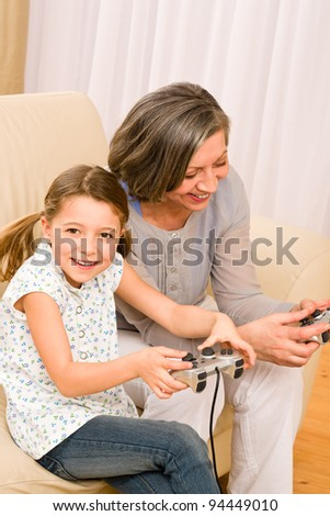 Grandmother play computer game with enthusiastic young girl have fun smiling - stock photo