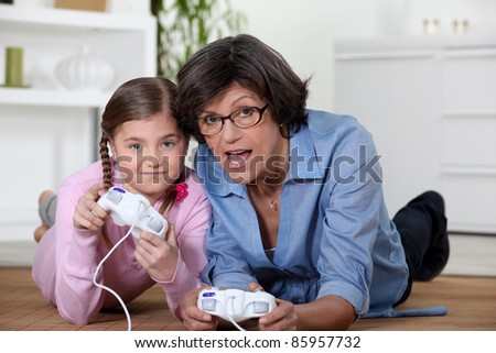 Grandmother playing a video game with her granddaughter - stock photo