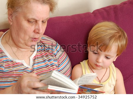 grandmother read the book for her grandson. - stock photo