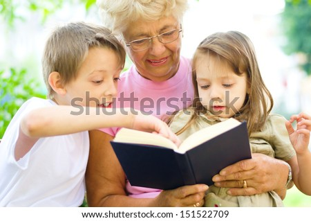 Grandmother reading  a book for grandchildren, outdoors - stock photo