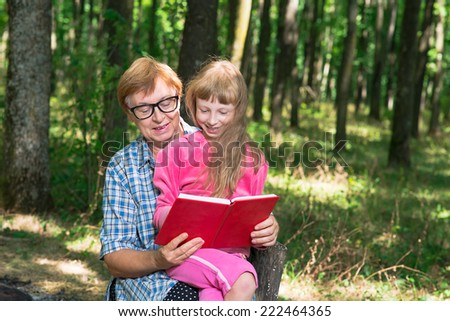 Grandmother reading a book to little girl in the woods - stock photo