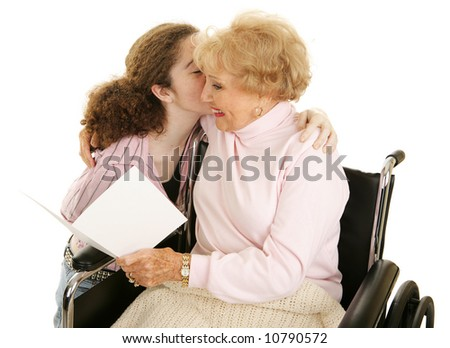 Grandmother reading a greeting card and getting a kiss from her teen-aged granddaughter.  Isolated on white. - stock photo