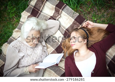 Grandmother reading a story to his granddaughter in the park - stock photo