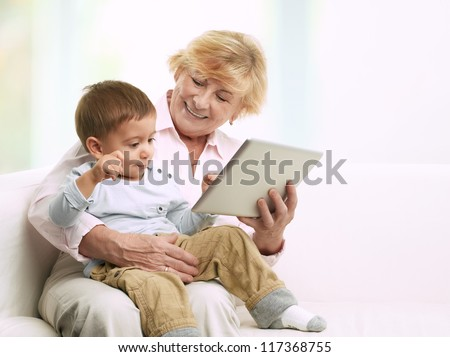 Grandmother reading a tale to her grandson from a digital tablet - stock photo