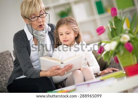 Grandmother reading interesting book her little granddaughter - stock photo