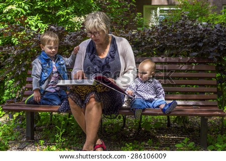 Grandmother reading to her grandchildren in the park - stock photo