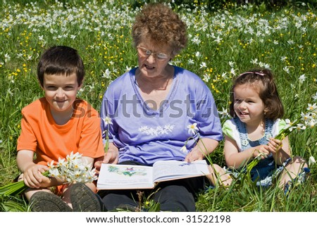 Grandmother reading to her happy grandchildren a tale - stock photo