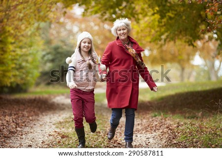 Grandmother Running Along Autumn Path With Granddaughter