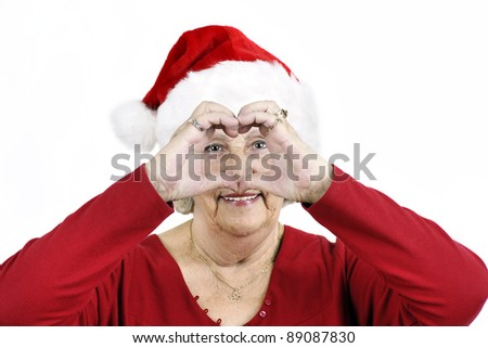 Grandmother sending her love for Christmas by making a heart shape with her hands while wearing Santa Claus hat. - stock photo