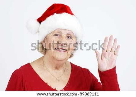 Grandmother sending her love for Christmas by waving her hand while wearing Santa Claus hat. - stock photo