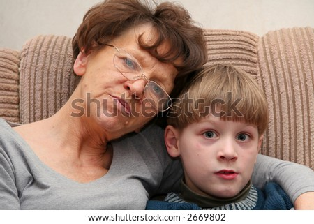 Grandmother sitting on the armchair with her grandchildren - stock photo