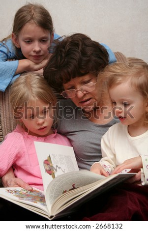 Grandmother sitting on the armchair with her grandchildren and reading - stock photo