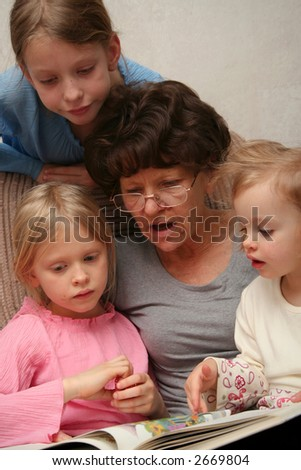 Grandmother sitting on the armchair with her grandchildren and reading