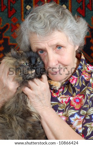 grandmother sitting with cat on her hands - stock photo