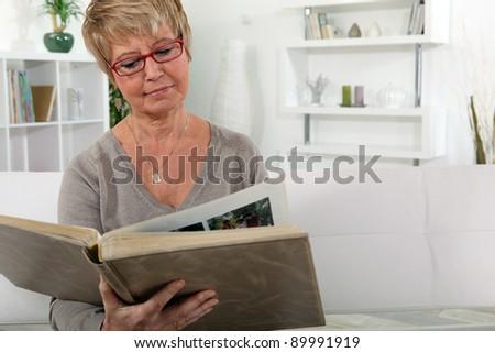 grandmother skimming through family album in lounge - stock photo