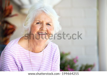 Grandmother smiling at camera with copyspace - stock photo