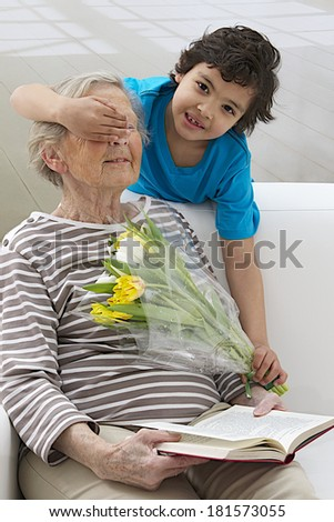 Grandmother surprise by grandson offering flowers - stock photo
