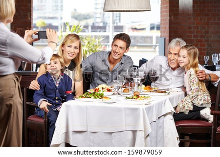 Grandmother taking family picture in restaurant with her smartphone