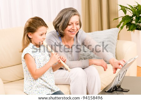 Grandmother teach young girl to play flute happy sitting on sofa - stock photo