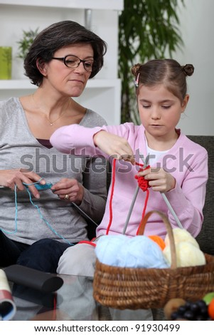 Grandmother teaching a little girl to knit - stock photo