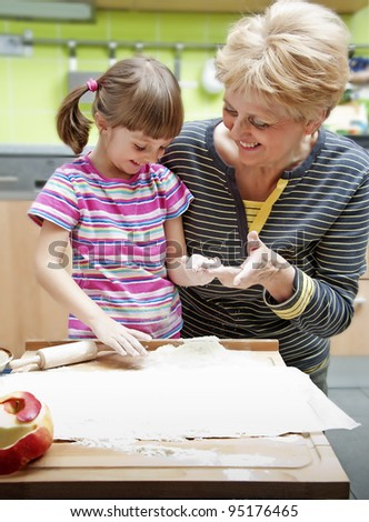 grandmother teaching her granddaughter cooking in home - stock photo
