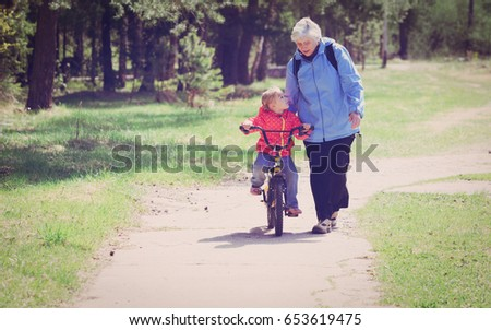 Grandmother teaching little granddaughter to ride bike