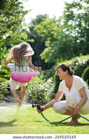 Grandmother watering garden, girl jumping over water jet