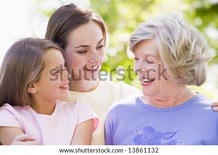 Grandmother with adult daughter and grandchild in park - stock photo