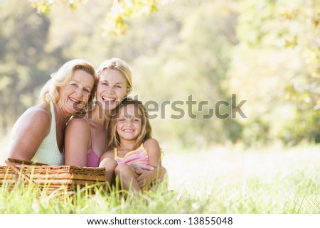 Grandmother with adult daughter and grandchild on picnic - stock photo