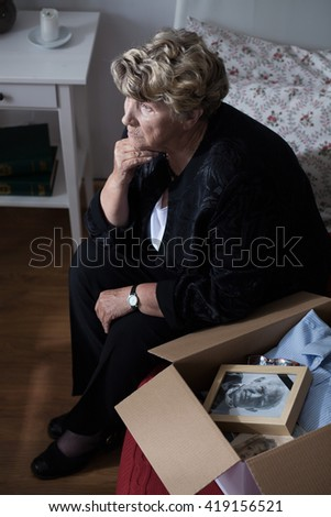 Grandmother with box of keepsakes of her lost husband - stock photo