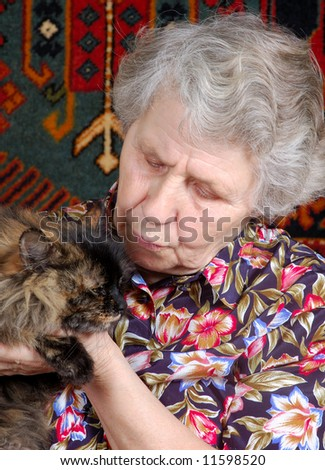 grandmother with cat on her hands - stock photo
