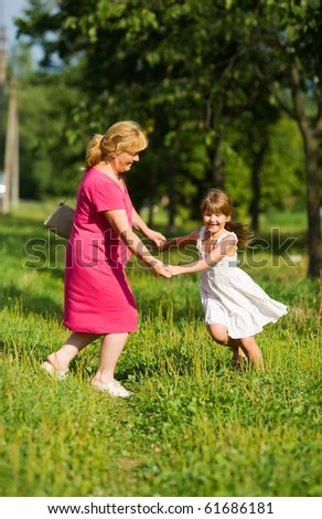 Grandmother with child dancing together outdoors - stock photo