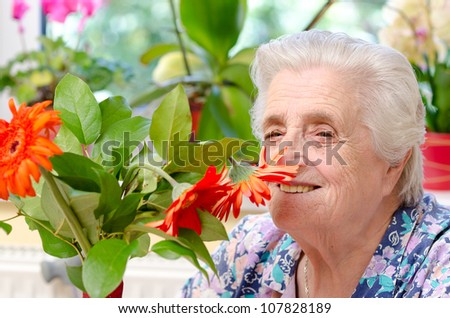 Grandmother with flowers - stock photo
