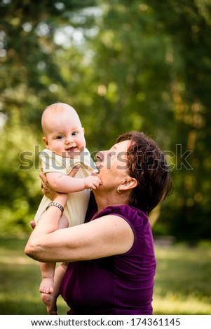 Grandmother with grandchild - senior woman holding her granddaughter outdoor in nature - stock photo