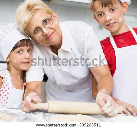 Grandmother with grandchildren baking cookies prepare dough - stock photo