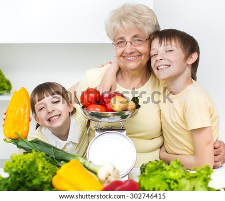 grandmother with grandchildren holding different vegetables - stock photo