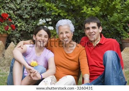 Grandmother with grandchildren in the garden - stock photo