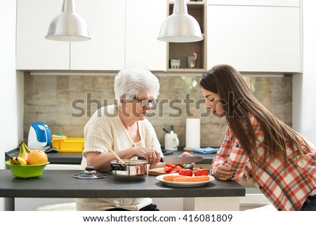Grandmother with granddaughter cooking in the kitchen. - stock photo