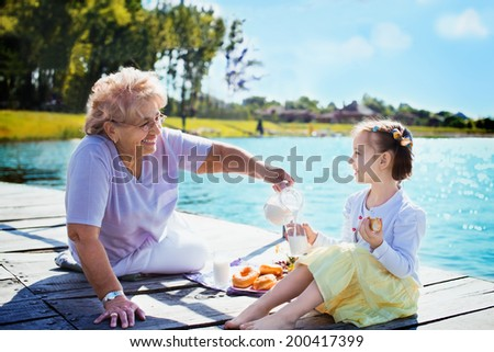 Grandmother with granddaughter eating breakfast on the lake - stock photo