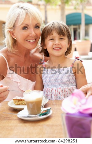 Grandmother With Granddaughter Enjoying Coffee And Cake In Cafe