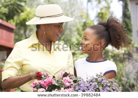 Grandmother With Granddaughter Gardening Together - stock photo