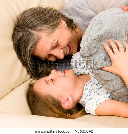 Grandmother with granddaughter hugging smiling together lying on sofa - stock photo