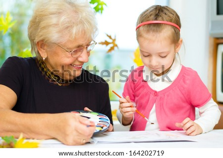 Grandmother with granddaughter painting with paintbrush and colorful paints, autumn background - stock photo