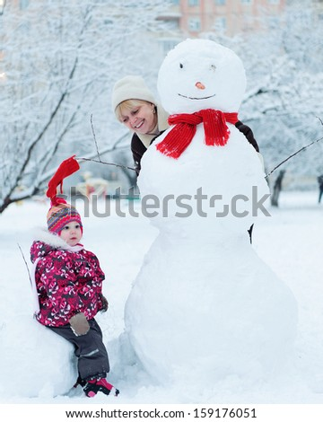 Grandmother with granddaughter playing in snow with snowman - stock photo